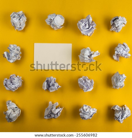Crumpled paper balls and blank sheet of paper on yellow background. Creativity problems. Searching ideas. Business Card - stock photo
