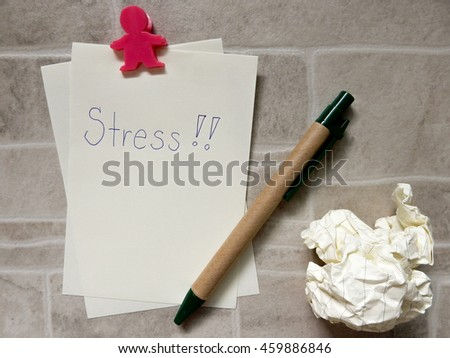 Crumpled paper balls and sheet of paper with stress word and pen - stock photo