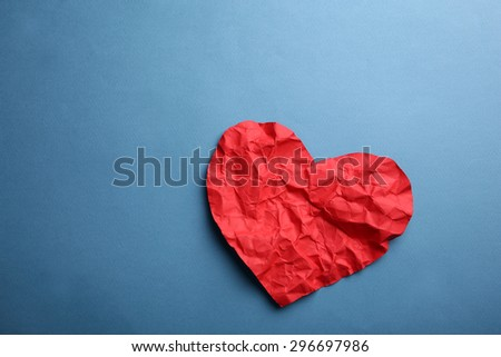 Crumpled paper heart on blue background - stock photo