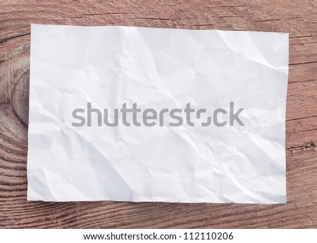 Crumpled paper sheet on a wooden background - stock photo