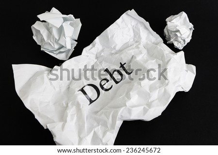 Crumpled paper sheet with word Debt isolated on black - stock photo
