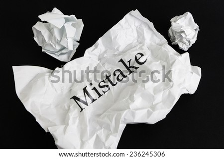 Crumpled paper sheet with word Mistake isolated on black - stock photo