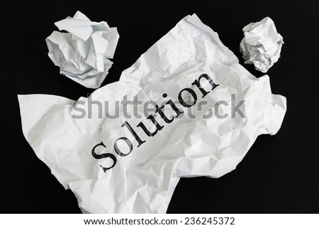 Crumpled paper sheet with word Solution isolated on black - stock photo