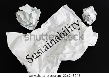 Crumpled paper sheet with word Sustainability isolated on black - stock photo