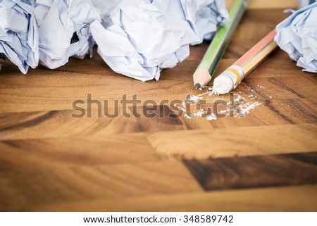 Crumpled papers and pencil eraser on wooden background - stock photo