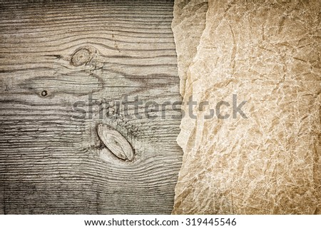 Crumpled parchment on wooden boards - stock photo