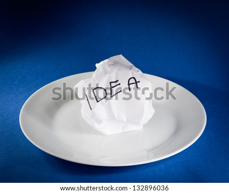 Crumpled piece of paper with idea written on it - stock photo