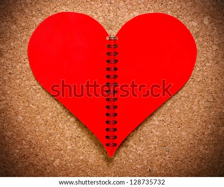 Crumpled red paper heart on cork background. Concept. - stock photo
