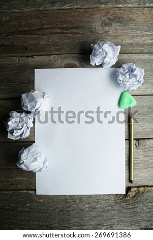 Crumpled up papers with a sheet of blank paper and a pencil on grey wooden background - stock photo