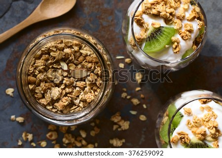 Crunchy almond and oatmeal granola in jar with yogurt kiwi granola parfait in glasses, photographed overhead with natural light (Selective Focus, Focus on the top of the granola and the parfaits)