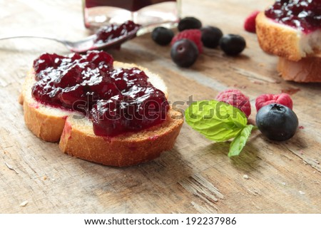 Crunchy bread with sweet jam on a wooden table - stock photo