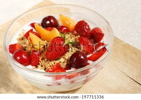 Crunchy fruit muesli (whole grain oats), served with fresh strawberries, apricot and cherry and low fat yogurt in a glass bowl - healthy summer breakfast - stock photo