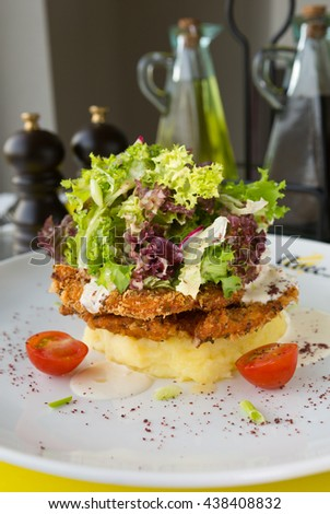 Crunchy golden fried free range chicken Escalopes, topped with a warm cream sauce, mashed potato and refreshing fresh green salad. - stock photo