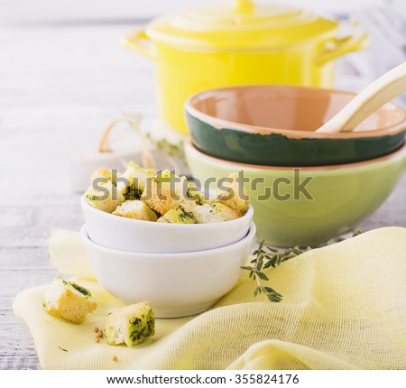 Crunchy homemade croutons with herbs and butter to the soup in a simple light wooden background. selective Focus