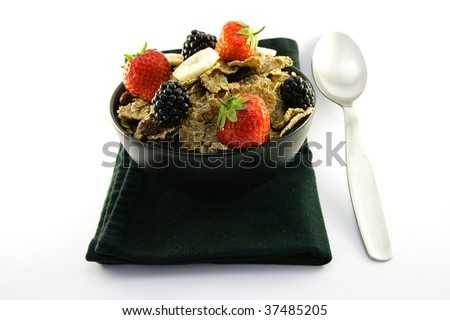 Crunchy looking delicious bran flakes and juicy fruit in a black bowl with a spoon on a black napkin on a white background