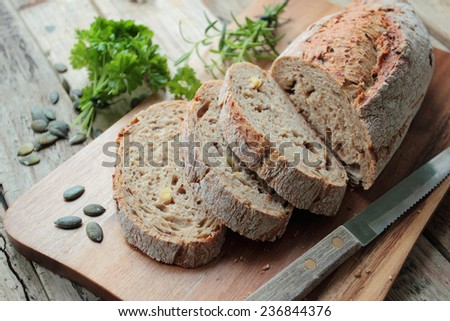 Crunchy wholemeal bread with knife on wooden cutting board - stock photo