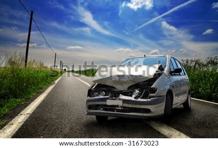 crushed car on a country road - stock photo