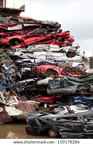 Crushed cars going to be shredded in a recycling facility - stock photo