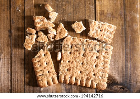 Crushed cookie on wooden background