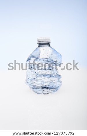 Crushed empty water bottle ready fro recycling. - stock photo