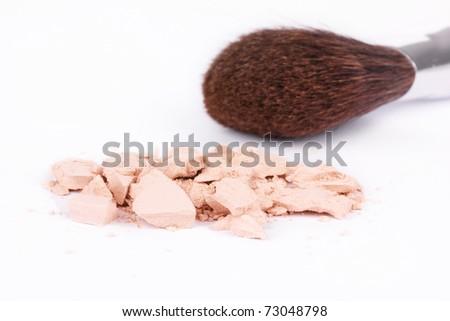 Crushed eyeshadows and make-up brush, closeup on white - stock photo