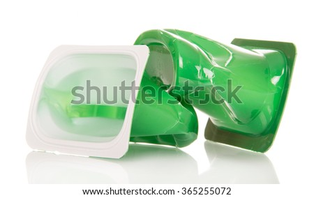 Crushed plastic cups of yogurt close up on a white background - stock photo