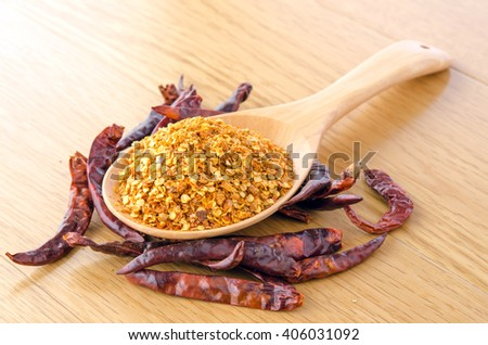crushed red chili pepper on wood spoon with dry red chili on wood table - stock photo