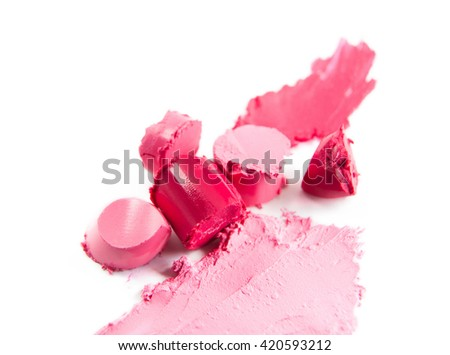 Crushed sliced pink lipstick isolated on white background. Texture of damaged pink colored lipstick on white. Pieces of colorful lipstick closeup.    - stock photo