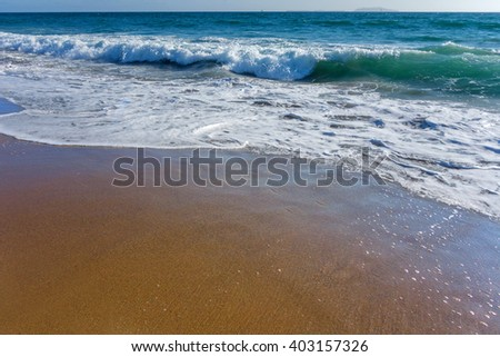Crushing waves with soapy suds coming from distant Channel Islands polish sands of Mandalay beach in Oxnard, Ventura county, Southern California - stock photo