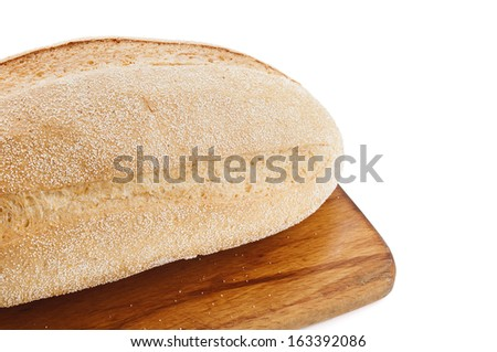 Crusty white loaf of cornbread on rustic wooden board - stock photo