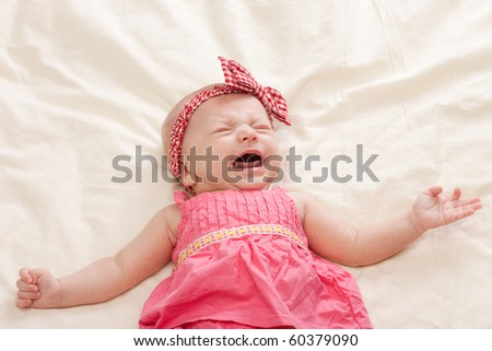 Crying and gesturing ten weeks old baby girl on bed - stock photo