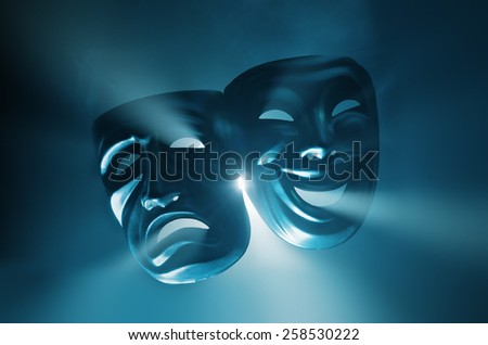 Crying and smiling masks in hazy light. - stock photo