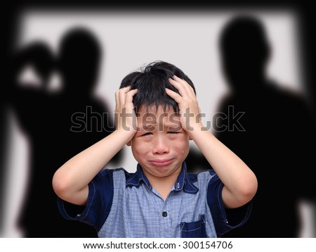 Crying asian boy with his fighting parents in the background - stock photo
