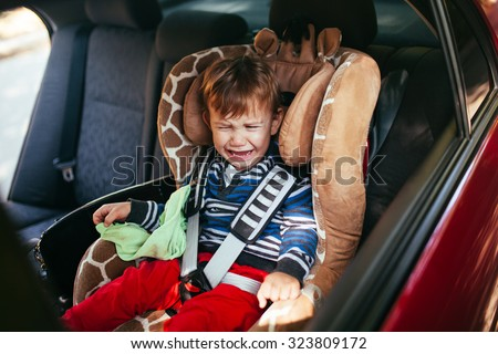 Crying baby boy in car seat.