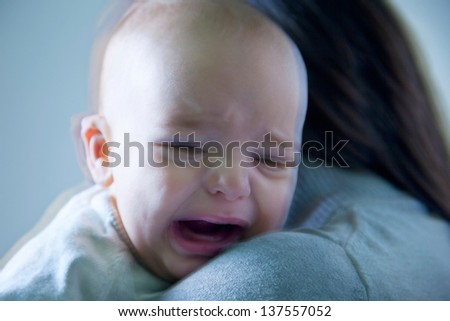Crying baby boy/ Little baby crying in the arms of mother - stock photo