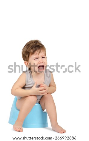 Crying baby boy sitting on a blue potty isolated on white background - stock photo