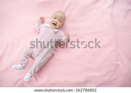 Crying baby girl on pink background - stock photo