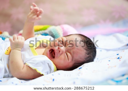 crying baby  lying in his bed - stock photo