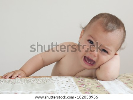 Crying baby or toddler child, boy or girl, at home leaning on bed. - stock photo