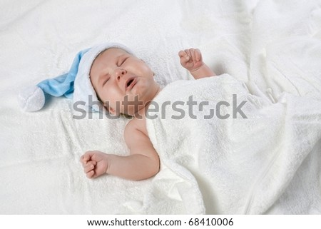 Crying baby with blue cap - stock photo