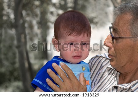 Crying baby with his gradpa - stock photo
