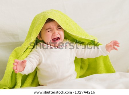 Crying Baby With Towel On The Head, Indoors - stock photo