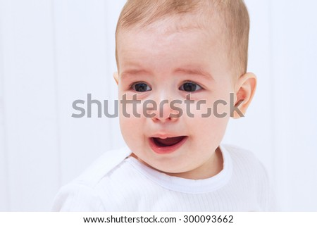 Crying beautiful baby on white background