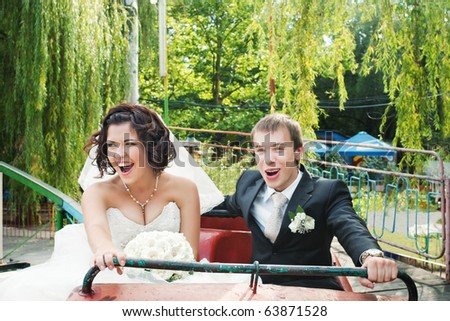 Crying bride and groom in rollercoaster cabin in blurred motion - stock photo