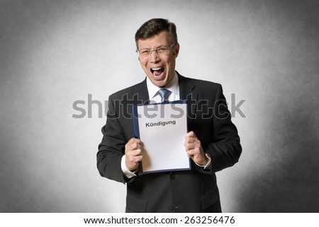 Crying business man holds a file with german text Kundigung (in engslish dismissal) - stock photo