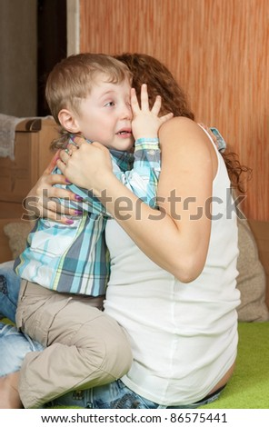 crying child and his careful mom in home interior - stock photo