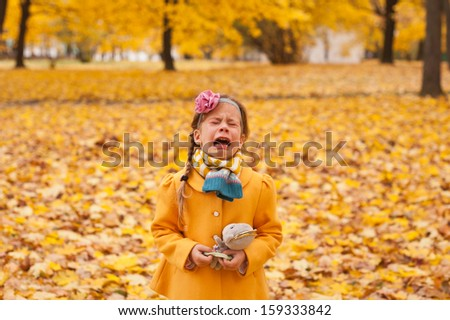 Crying child girl walking alone in autumn forest - stock photo