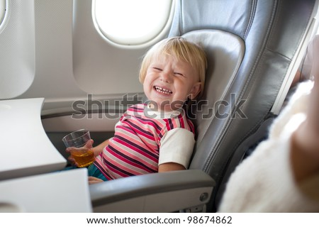 crying child with juice in airplane - stock photo