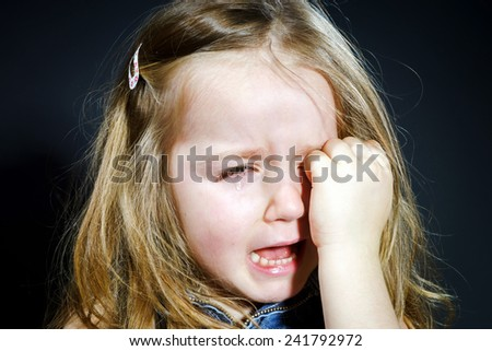 Crying cute little girl with focus on her tears on dark background - stock photo