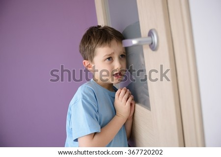 Crying, frightened child listening to a parent talking through the door with a glass pressed to his ear. - stock photo